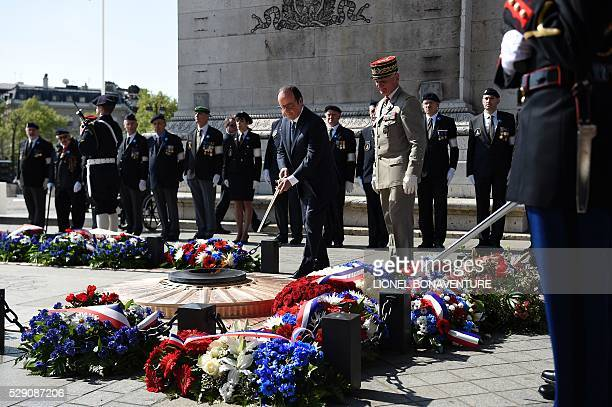 French President Francois Hollande rekindles the eternal flame at the Tomb of the Unknown Soldier during a ceremony marking the 71st anniversary of...