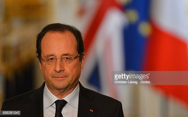 French President Francois Hollande right and British Prime Minister David Cameron adjust their earpieces during a press conference at the Elysee...