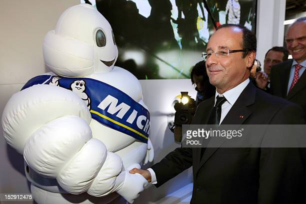 French President Francois Hollande shakes hand with French tire maker Michelin mascot Bibendum during a visit at the Paris Motor Show on September 28...
