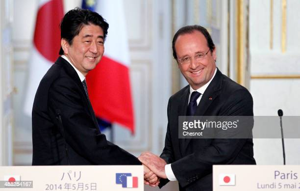 French President Francois Hollande shakes hand with Japanese Prime Minister Shinzo Abe after a joint press conference at the Elysee presidential...