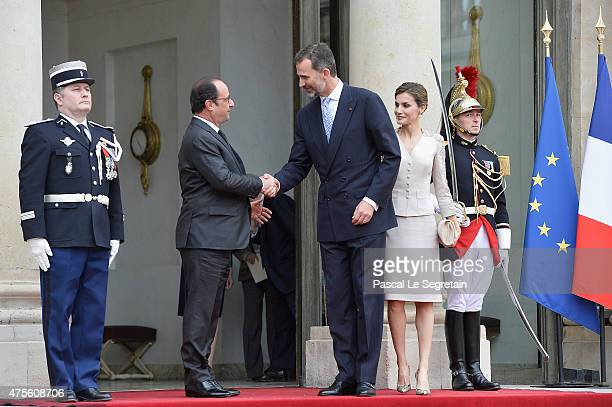 French President Francois Hollande shakes hand with King Felipe VI of Spain watched by Queen Letizia of Spain in the courtyard of the Elysee Palace...