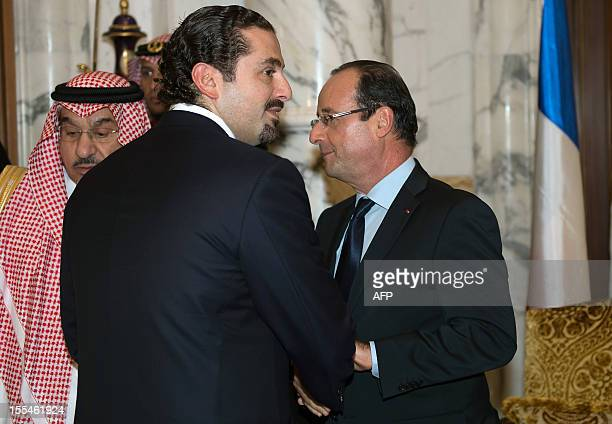 French President Francois Hollande shakes hand with Lebanon's former prime minister Saad Hariri after a meeting with Saudi Arabia's King Abdullah bin...