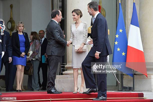 French President Francois Hollande shakes hand with Queen Letizia of Spain watched by King Felipe VI of Spain in the courtyard of the Elysee Palace...