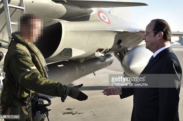 French President Francois Hollande shakes hands with an air force pilot during a visit to French servicemen at the AlDhafra 104 airbase in the United...