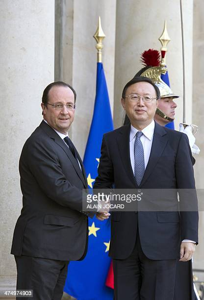 French President Francois Hollande shakes hands with Chinese State Councilor Yang Jiechi upon his arrival at the Elysee presidential palace on...
