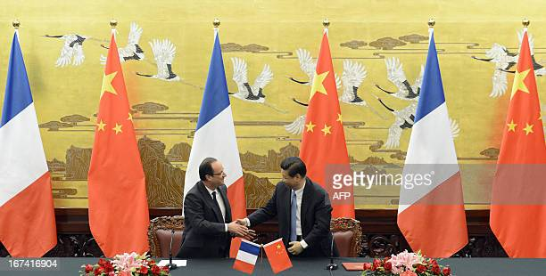 French President Francois Hollande shakes hands with Chinese President Xi Jinping during a press conference at the Great Hall of the People in...
