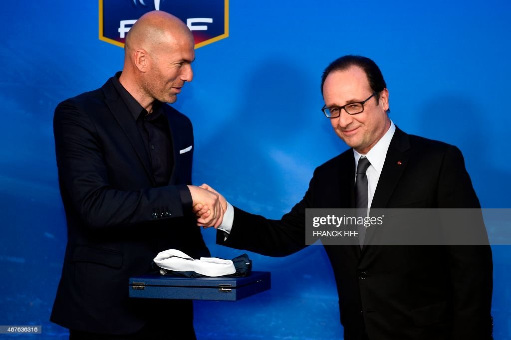 French president Francois Hollande (R) shakes hands with Former French international football player Zinedine Zidane during a ceremony honouring French former international football players with more than hundred caps ahead of the friendly football match France vs Brazil, on March 26, 2015 at the Stade de France in Saint-Denis, north of Paris. AFP PHOTO / FRANCK FIFE / AFP PHOTO / Franck FIFE