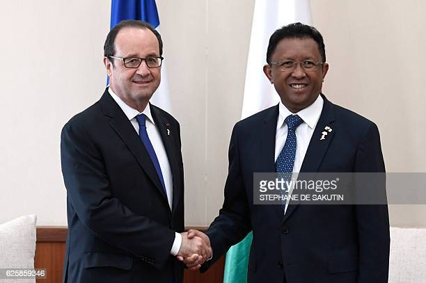 French President Francois Hollande shakes hands with Madagascar President Hery Rajaonarimampianina during the 16th 'Sommet de la Francophonie' on...