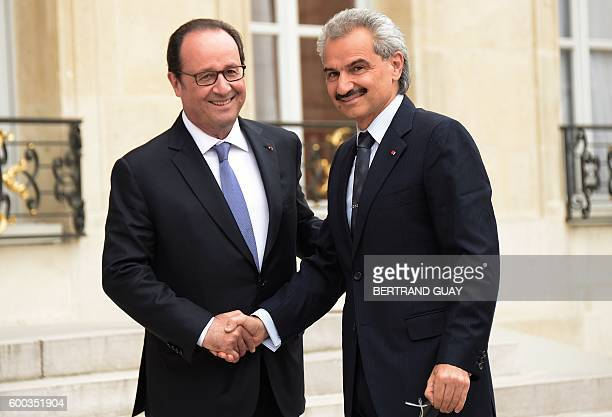 French President Francois Hollande shakes hands with Saudi Prince Al Waleed bin Talal bin Abdulaziz Al Saoud at the Elysee Presidential Palace before...