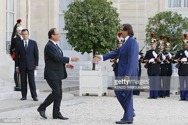 French President Francois Hollande shakes hands with the Emir of Qatar Sheikh Hamad bin Khalifa AlThani before a meeting about Syrian crisis at the...