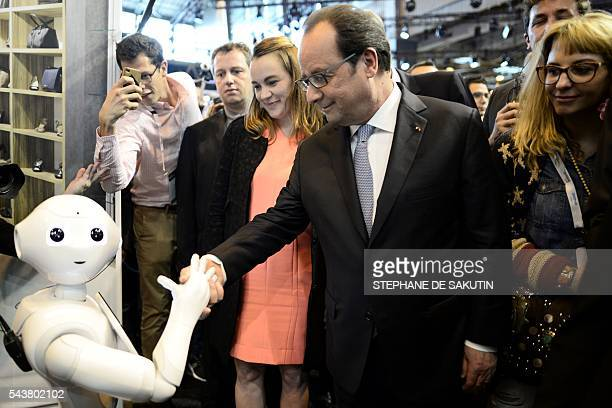 French President Francois Hollande shakes hands with the IBM Watson powered robot during his visit to the Viva technology event in Paris on June 30...
