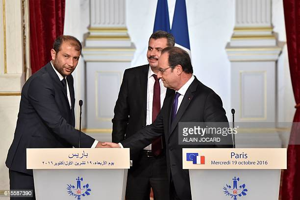 French President Francois Hollande shakes hands with White Helmet leader Raed Saleh next to Hagi Hasan Brita president of the civil committee of...
