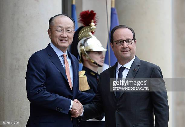 French President Francois Hollande shakes hands with World Bank President Jim Yong Kim upon his arrival at the Elysee Palace before a meeting on...