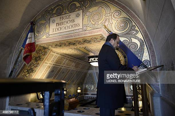 French President Francois Hollande signs a book of remembrance after paying his respects at the tombs of the WWI unknown soldiers in the crypt of the...