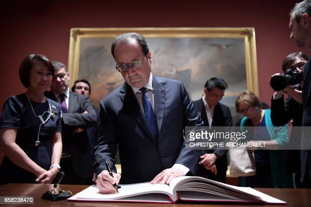 French President Francois Hollande signs a visitors' book during a visit the national gallery of Singapore in Singapore on March 27 2017 Hollande is...
