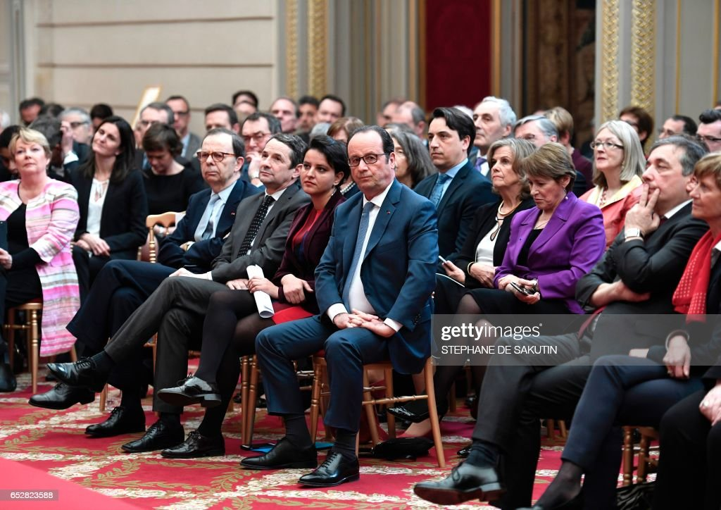 French President Francois Hollande (C) sits next to French Minister of Education Najat Vallaud-Belkacem as they attend an IDEX / ISITE event on March 13, 2017 at the Elysee Presidential Palace in Paris. /