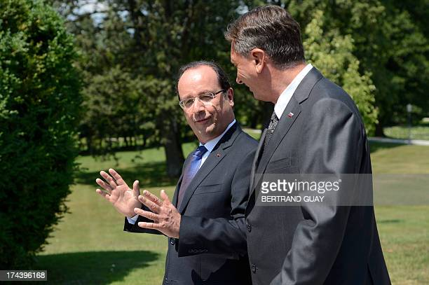 French President Francois Hollande speaks to his Slovenian counterpart Borut Pahor after posing for a group photo during The Leaders' Meeting of Brdo...