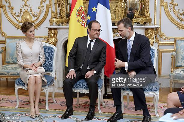 French President Francois Hollande speaks to Spain's King Felipe VI and Queen Letizia during a meeting at the Elysee presidential Palace in Paris on...