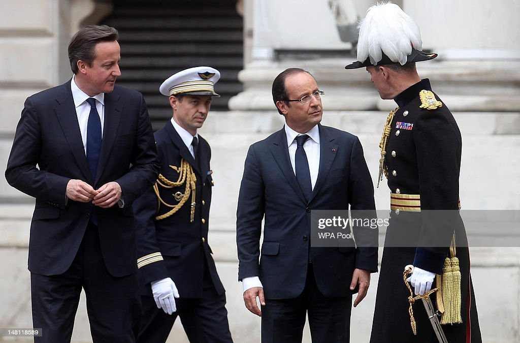 French President Francois Hollande (2nd R) speaks to the Major-General George Norton, the General Officer Commanding London District (R) while Prime Minister David Cameron (L) looks on outside the Foreign and Commonwealth Office on July 10, 2012 in London, England. This is the French President's first official visit to the United Kingdom, during which he will attend meetings with British Prime Minister David Cameron and Queen Elizabeth II.