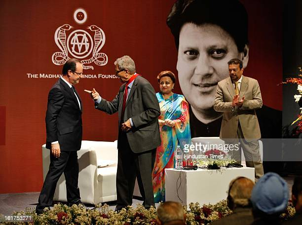 French President Francois Hollande speaks with Indian Nobel laureate Amartya Sen as Madhavi Raje Scindia and Vir Sangvi looks on after presenting him...