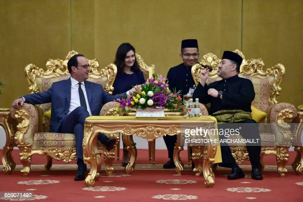 French President Francois Hollande speaks with Malaysia's King Sultan Muhammad V ahead of a state dinner at the Royal Palace in Kuala Lumpur on March...