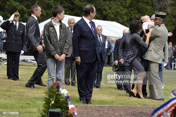 French President Francois Hollande standing next to a teenager looks behind him as a woman faints in front the French Resistance National monument on...