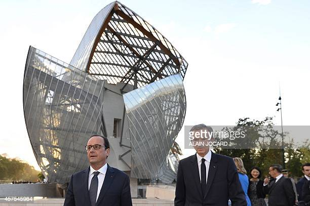 French President Francois Hollande stands next to Bernard Arnault who heads up the LVMH luxury goods empire during the inauguration of the Louis...