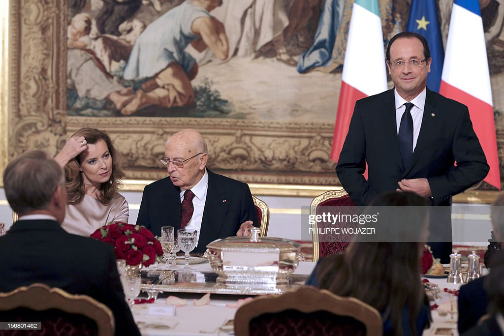 French President Francois Hollande (R) stands to deliver a speech as Italian President Giorgio Napolitano (C) speaks with Hollande's companion Valerie Trierweiler during a state dinner at the Elysee Palace in Paris, on November 21, 2012. President Napolitano is on a two-day state visit in Paris.