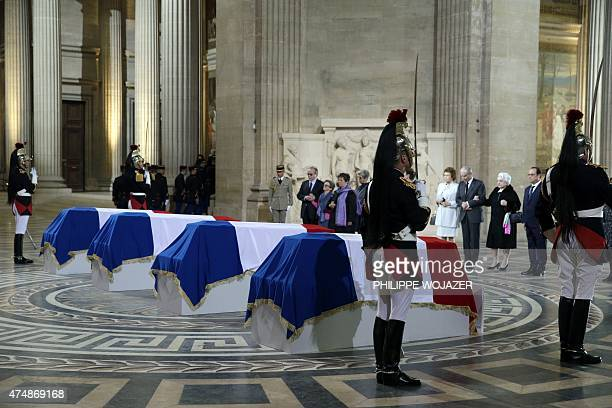 French President Francois Hollande stands with family members as they pay their respects in front of four flagdraped caskets representing World War...