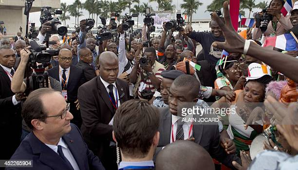 French President Francois Hollande surrounded by security and reporters is greeted by wellwishers upon his arrival in Abidjan on July 17 2014...