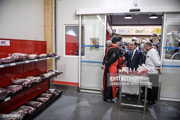 French President Francois Hollande talks with an organic meat producer as he visits the new organic market hall during its inauguration at the...
