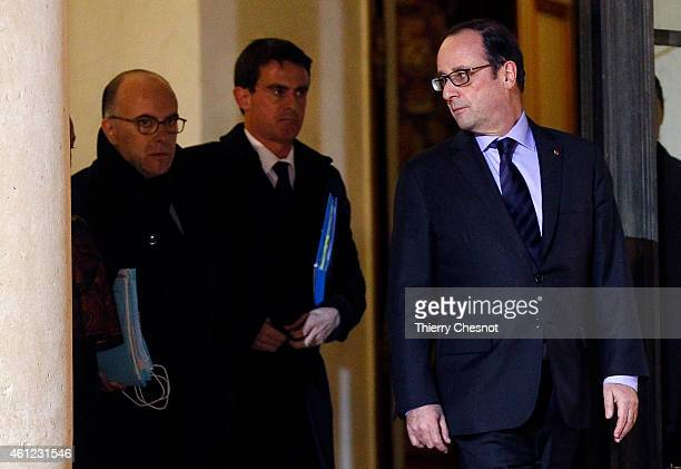 French President Francois Hollande talks with French Prime Minister Manuel Valls next to French Interior Minister Bernard Cazeneuve after holding a...