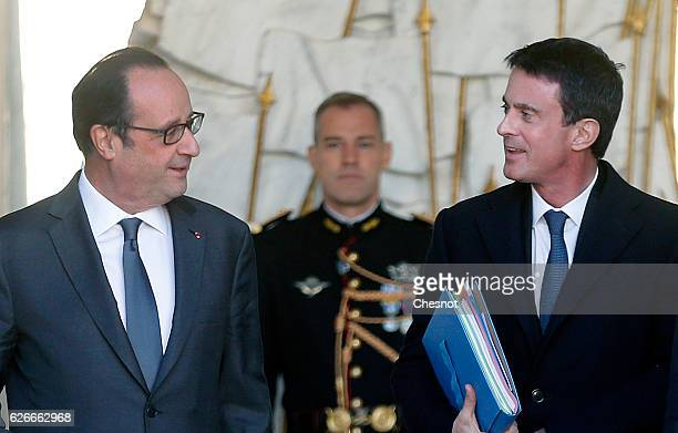 French President Francois Hollande talks with French Prime minister Manuel Valls after the weekly cabinet meeting at the Elysee Presidential Palace...