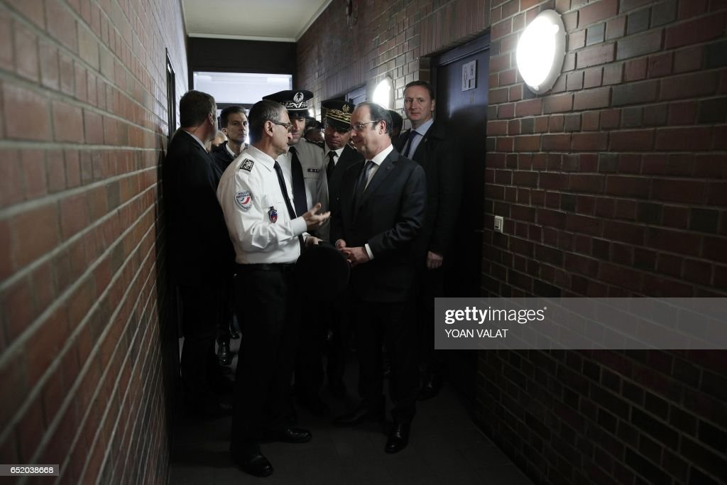 French President Francois Hollande (C) visits a police station before a ceremony to unveil the plaque of a street named after former Aubervilliers' mayor, Jacques Salvator, on March 11, 2017 in Aubervilliers, north of Paris. Jacques Salvator died on March 11, 2016. /