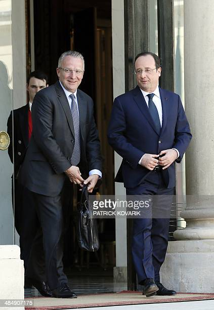 French President Francois Hollande walks next to the president of the national agribusiness industry association JeanPhilippe Girard after their...