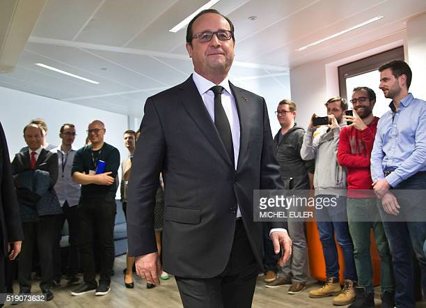 French President Francois Hollande walks past employees as he visits a tech company in BoulogneBillancourt outside Paris on April 4 2016 Hollande...