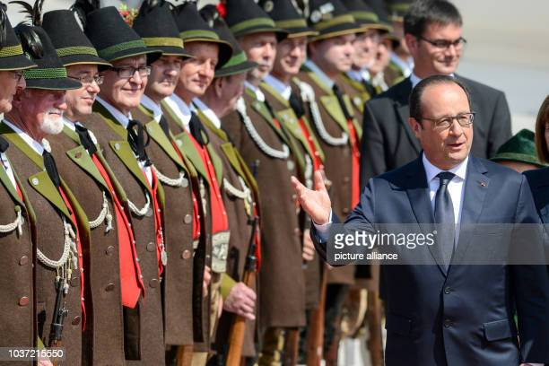 French President Francois Hollande walks past the Gebirgsschuetzen the traditional Bavarian militia after arriving at the airport in Munich Germany...