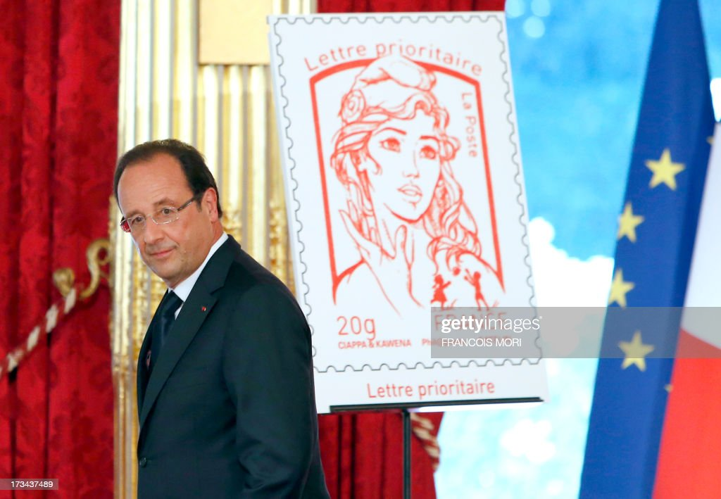 French President Francois Hollande walks past the new official Marianne, the symbol of the French republic, postage stamp on July 14, 2013 after unveiling it at the presidential Elysee Palace in Paris during Bastille Day celebrations.