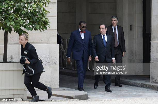 French President Francois Hollande walks with African Development Bank President Akinwumi Adesina during the « 4ème Business Dialogue de haut niveau...