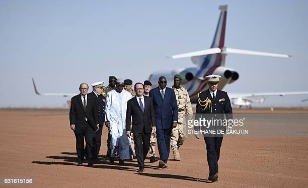 French President Francois Hollande walks with Malian Prime Minister Modibo Keita French Defence Minister JeanYves Le Drian and Chief of the Defence...