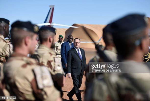 French President Francois Hollande walks with Malian Prime Minister Modibo Keita as he arrives on January 13 2017 to visit the troops of France's...