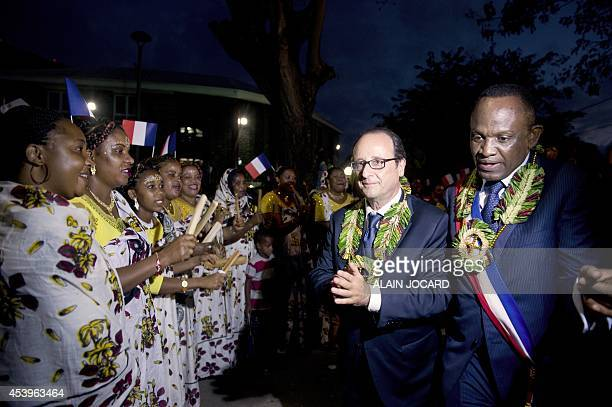 French President Francois Hollande walks with mayor of Dzaoudzi Said Omar Oili after delivering a speech on August 22 2014 in Dzaoudzi as part of a...