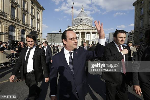 French President Francois Hollande waves to the crowd as he walks in the street as he leaves the Pantheon with bodyguards after a ceremony in Paris...