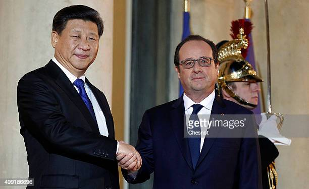 French President Francois Hollande welcomes Chinese President Xi Jinping prior to attend a working dinner at the Elysee Presidential Palace on...