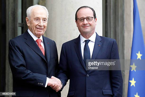 French President Francois Hollande welcomes former Israeli President Shimon Peres prior a meeting at the Elysee Palace on 18 December 2014 in Paris...