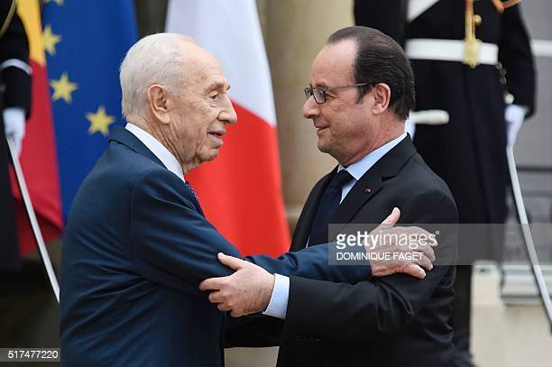 French President Francois Hollande welcomes former Israeli President Shimon Peres before their meeting at the Elysee Palace in Paris, on March 25,...