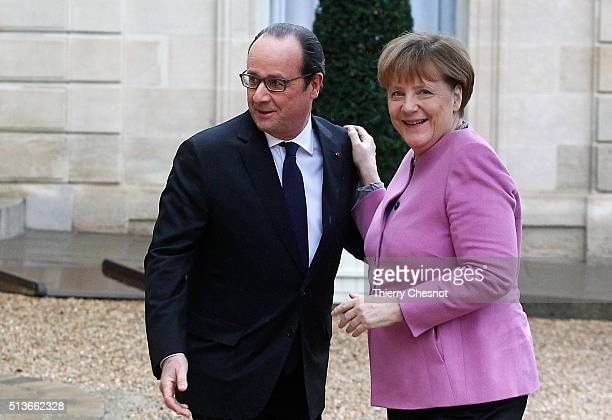 French President Francois Hollande welcomes German Chancellor Angela Merkel prior to attend a meeting at the Elysee Presidential Palace on March 04...