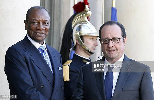 French President Francois Hollande welcomes Guinean President Alpha Conde prior to a meeting at the Elysee Palace on April 22 2015 in Paris France