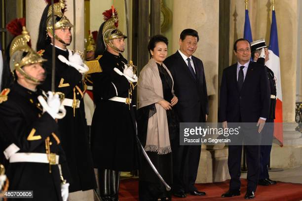 French President Francois Hollande welcomes the Chinese President Xi Jinping and his wife Peng Liyuan at the Elysee Palace for an official dinner...