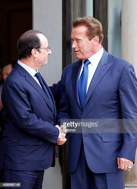French President Francois Hollande welcomes US actor, former governor of California and founding chair of the R20 initiative Arnold Schwarzenegger...